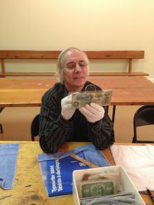 Adrian inspecting an old bank note
