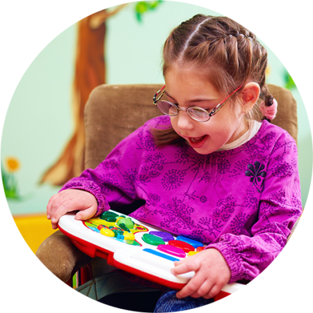 Young girl wearing glasses playing with a colourful toy with touch buttons on it