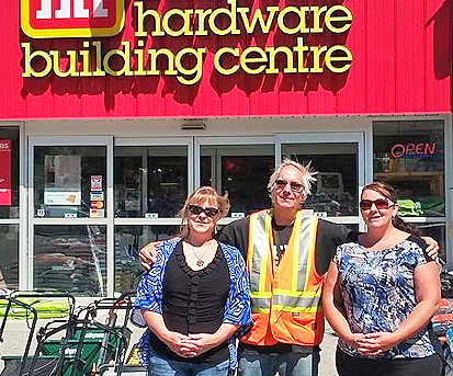 two ladies and a man standing in front of a hardware store
